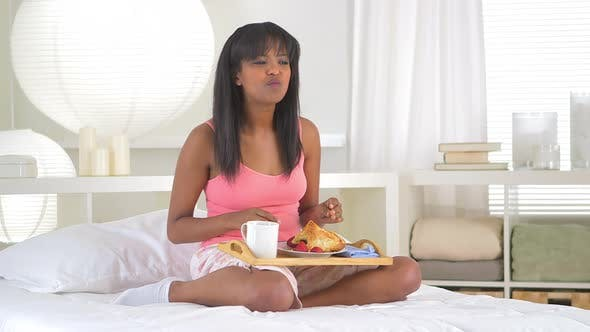 African American girl eating breakfast in bed