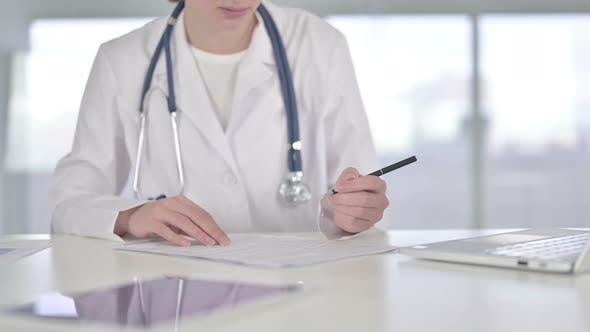 Thumbnail for Close Up of Young Doctor Doing Paperwork in Office