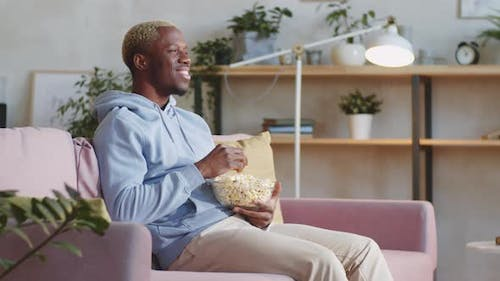 Black Man Eating Popcorn and Watching Comedy Movie at Home