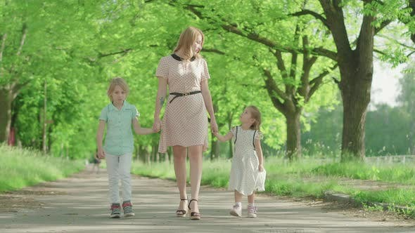 Thumbnail for Wide Shot of Young Positive Mother Strolling Outdoors with Children. Cute Little Girl and Boy