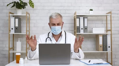 Doctor At Laptop Wearing Face Mask Consulting Patient Online Indoor
