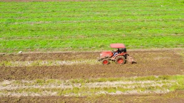 Ein Landwirt benutzt einen Traktor, um den Boden für den Reisanbau vorzubereiten