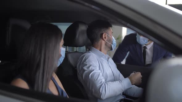 Thumbnail for Masked Couple Enjoying Sitting in New Bought Car