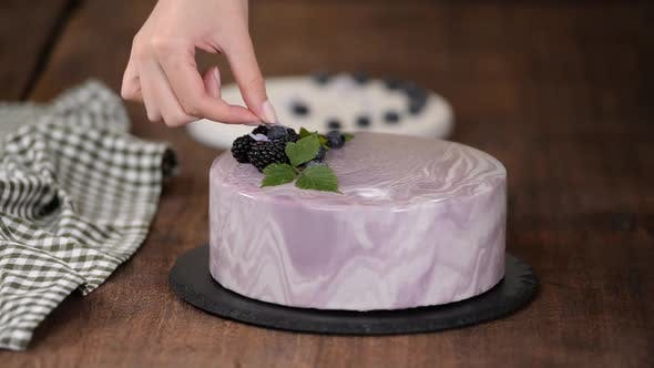 Thumbnail for Women's Hands Decorate a Berry Mousse Cake with with Flowers on the Kitchen Table.