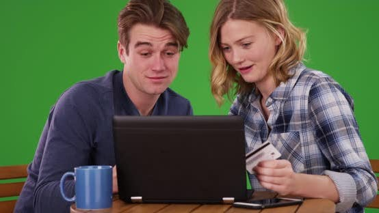 Thumbnail for Male and female sitting at table in backyard using laptop on green screen