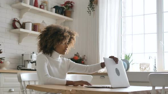 Dark Skinned Lady Sits at Table and Opens Laptop in Kitchen