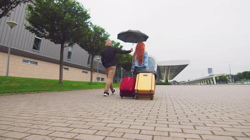 A Woman Carrying Two Suitcases To the Airport Terminal and a Man Holding an Umbrella. The Priority
