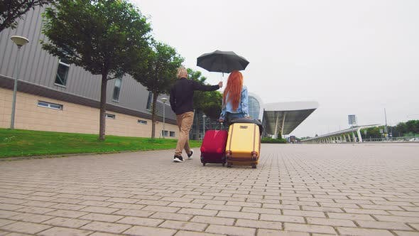 Thumbnail for A Woman Carrying Two Suitcases To the Airport Terminal and a Man Holding an Umbrella. The Priority