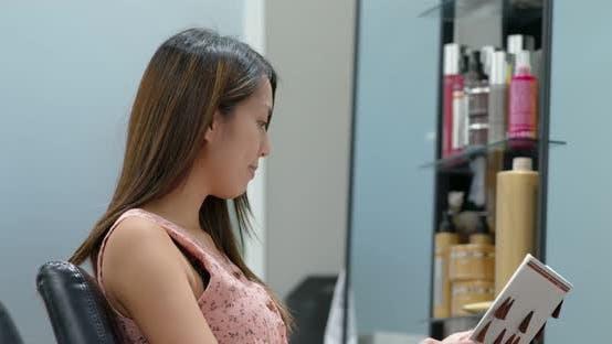 Femme regarder le livre de couleur de cheveux pour choisir la couleur de teinture au salon de beauté