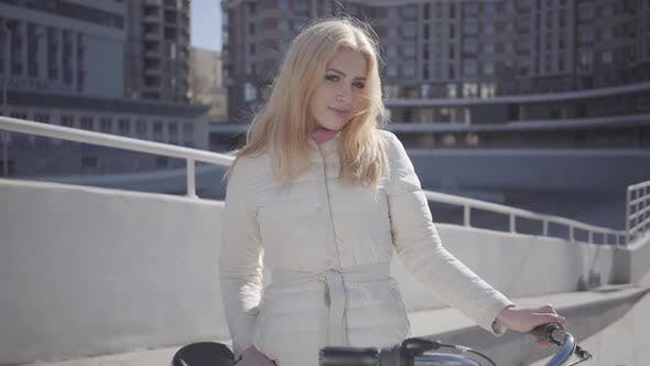 Thumbnail for Portrait Pretty Blond Woman in Warm White Jacket Standing at the City Street with Bicycle Looking in