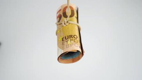 Rolle europäischer Geldscheine, die mit einem Gummiband verbunden sind, das auf weißem Hintergrund schwingt