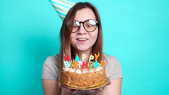 Thumbnail for Concept of Celebration and Fun. Young Cheerful Funny Girl with a Birthday Cake