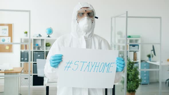 Slow Motion of Doctor in Protective Suit Standing in Empty Office with Stayhome Poster