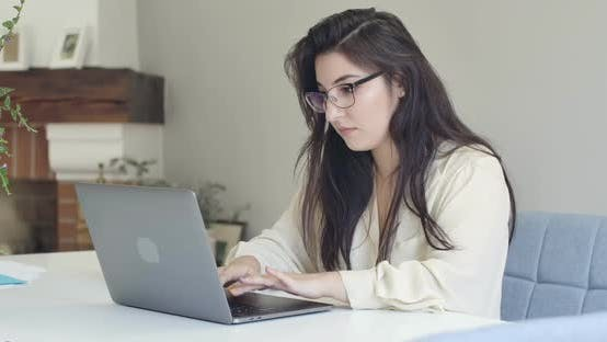Cover Image for Portrait of Young Intelligent Caucasian Woman in Eyeglasses Typing on Laptop and Drinking Tea or