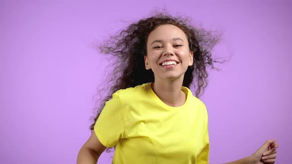 Young Cute Woman Smiling and Dancing on Violet Studio Background