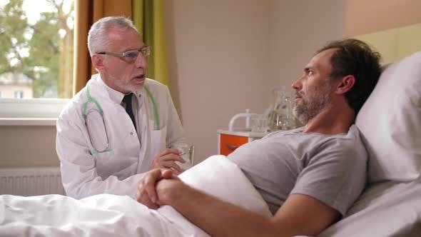 Cover Image for Aging Physician Examining Sick Male Lying in Ward