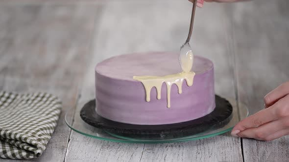Cover Image for Preparation of a holiday cake. The girl pours liquid white chocolate.