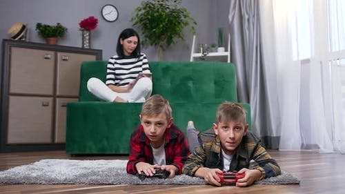 Woman Sitting on Couch and Using i-pad while Her Two Happy Handsome Carefree Sons Playing Video Game