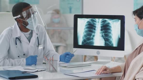Schwarzer Arzt in Schutzuniform diskutiert Röntgen mit Frau