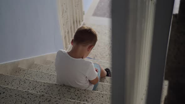Thumbnail for Offended Child Sitting on the Stairs