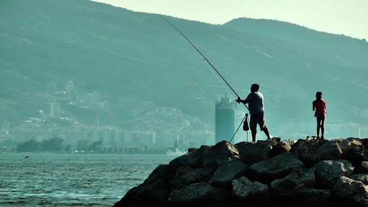 Thumbnail for Fisherman and Child Silhouettes on Rocks