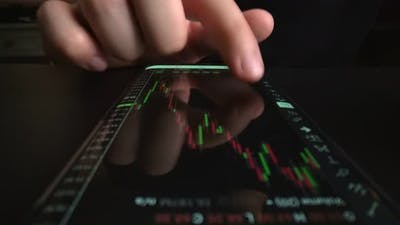 Businessman reading stock market chart on mobile phone, trading online.