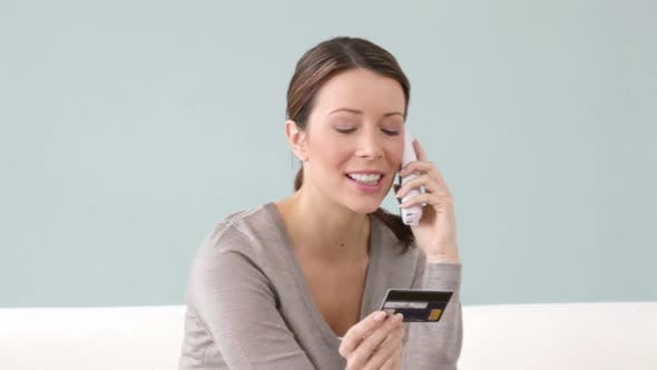 Thumbnail for Young woman on the phone with credit card
