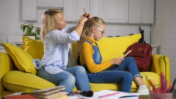Mother Tying Daughter's Long Hair Before School