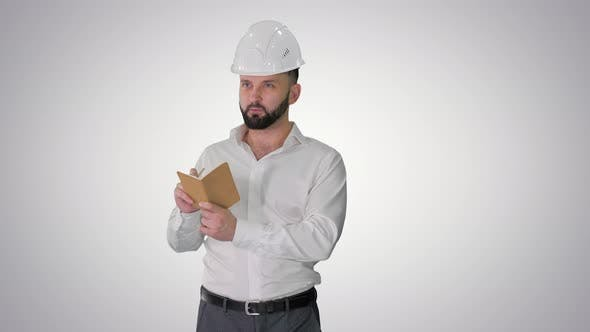 Confident Mature Man in Formalwear and Hardhat Writing Down Notes on Gradient Background