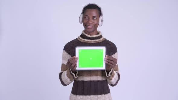 Thumbnail for Young Happy African Man Thinking While Showing Digital Tablet Ready for Winter