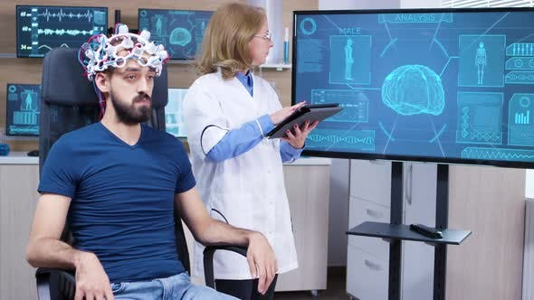 Cover Image for Female Neurologist Reading Data From Brainwave Scanning Headset
