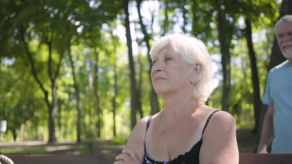 Thumbnail for Portrait of an Attractive Mature Woman Sitting on the Bench in the Park