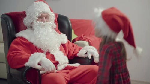 Merry Christmas! Little Girl Plays And Receives Gifts From Santa Claus