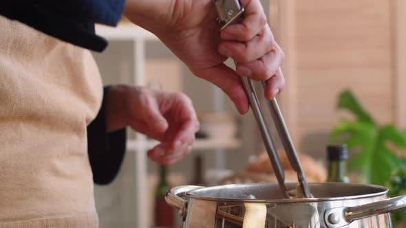 Thumbnail for Close Up of Man Using Tongs while Cooking Spaghetti