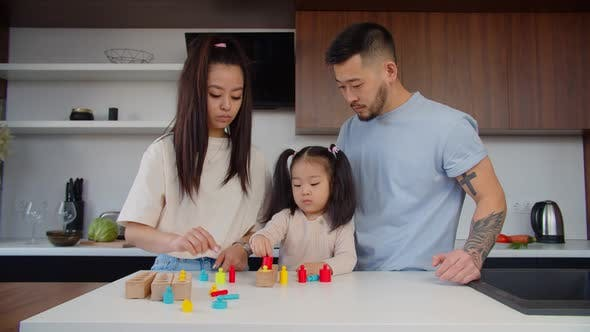 Asian Toddler Girl Playing with Sorter Puzzle Together with Parents