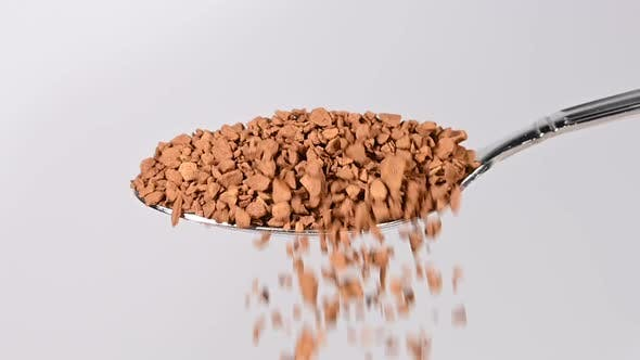 Pouring freeze-dried instant coffee from spoon