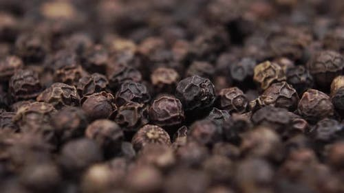Peppercorns falling close up with rotation