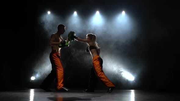 Thumbnail for Development of Straight Kicks Kickboxing on Boxing Paws. Light From Behind. Smoke Background