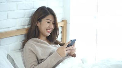Asian woman in bed checking social apps with smartphone.
