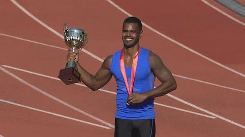 Muscular sportsman showing his medal and cup for victory to fans on stands
