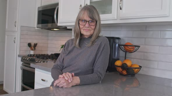 Thumbnail for Grey haired senior woman with glasses looking at camera at her kitchen counter