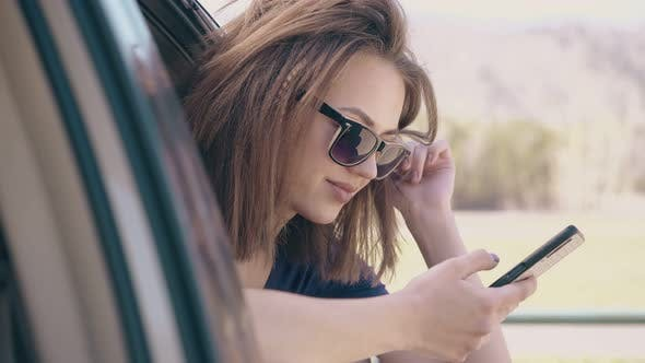Thumbnail for Girl Scrolls News Feed on Phone Leaning Out of Car Closeup