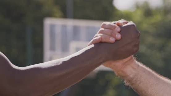 Thumbnail for Caucasian and African Men Holding Hands As Symbol of Unity at Outdoor Basketball Court