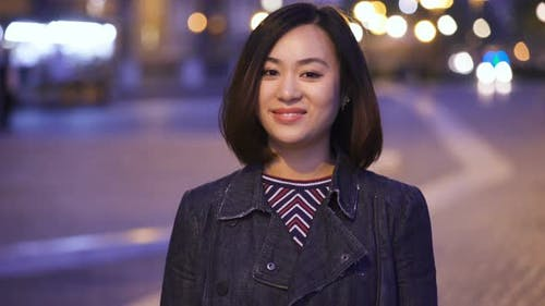 20 year old happy Chinese woman smiles at the camera,in the street at night