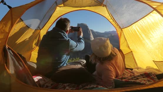 Thumbnail for A Couple in Love Takes a Selfie in a Yellow Touristic Tent at a Dawn in Yosemite Valley. USA