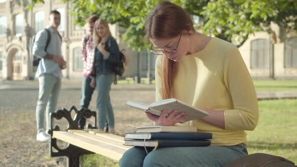 Thumbnail for Concentrated Redhead Girl in Eyeglasses Reading Book As Blurred Groupmates Laughing at Her at the