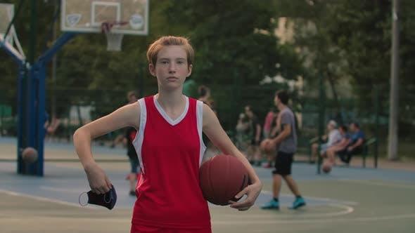 Teenage Girl steht auf einem Stadtspielplatz mit einem Basketball in einer medizinischen Maske. Der Basketballspieler