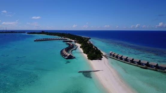 Wide angle birds eye tourism shot of a sunshine white sandy paradise beach and turquoise sea backgro