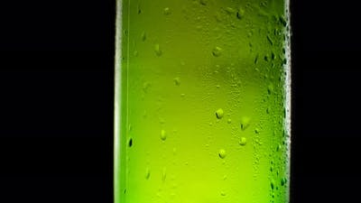 A Bottle of Cold Beer Swirls with Drops of Water