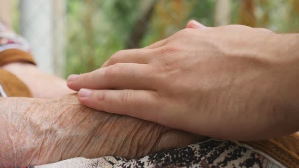 Thumbnail for Young Male and Wrinkled Hands Comforting and Stroking Each Other Outdoor. Grandson and Grandmother